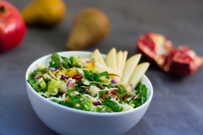A mixed green and kale salad mixed with pomegranate and pears
